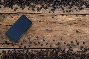 Smartphone und Kaffeebohnen auf dem Schreibtisch