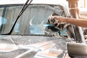 Das Personal der Autowaschanlage verwendet einen Schwamm, um die Windschutzscheibe zu reinigen