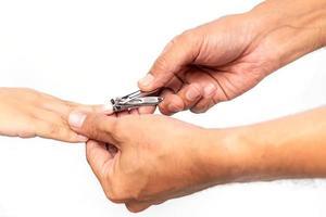 die Nägel eines Kindes abschneiden