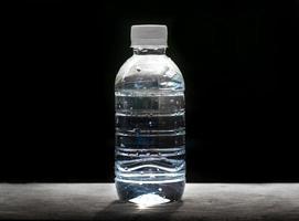 Wasserflasche auf schwarzem Hintergrund foto