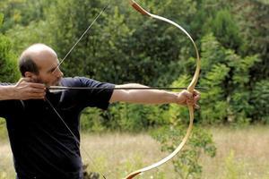 Mann schießt mit Bogen