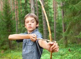 Kind mit hausgemachtem Pfeil und Bogen foto