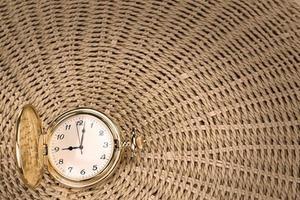 antike Taschenuhr auf einem strukturierten gewebten Strohhalm. Nahansicht.