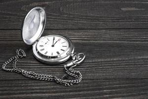 alte Taschenuhr mit Kette auf einem Holztisch liegend.