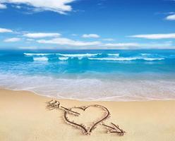 Herz mit Pfeil, als Liebeszeichen, gezeichnet am Strand. foto