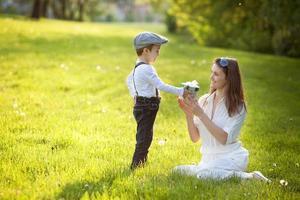 schönes Kind und Mutter im Frühlingspark, Blume und Geschenk foto