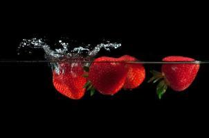 Erdbeeren spritzen ins Wasser foto
