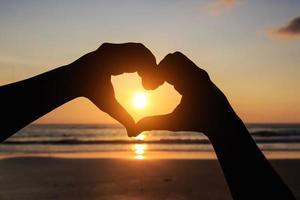 Silhouette der Hände im Herzsymbol um die Sonne