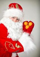 Der Weihnachtsmann zeigt ein Herz aus Mandarinen.