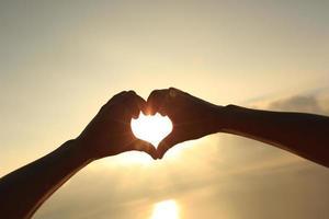 Herzform, die Hände gegen hellen Sonnenaufgang des Meeres macht