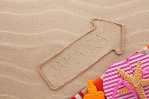 Jamaika Zeiger und Strandzubehör auf dem Sand liegen
