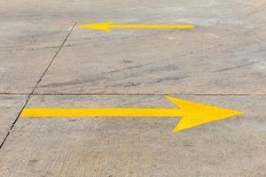 gelber Verkehrspfeil auf Betonstraße foto