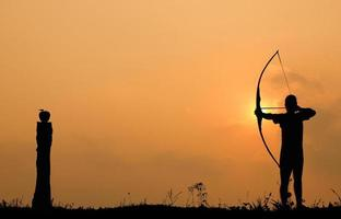 Silhouette Bogenschießen schießt einen Bogen auf einen Apfel auf Holz foto