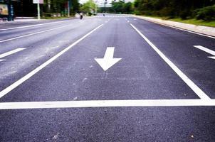 weiß lackierter Pfeil auf schwarzer Asphaltstraße