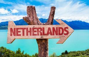 Holzschild der Niederlande Flagge mit Fluss auf Hintergrund foto