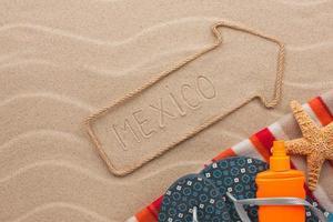 Mexiko Zeiger und Strandzubehör liegen auf dem Sand