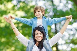 fröhlicher Junge mit Mutter, die auf Frühlingspark spielt. foto