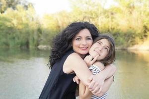 Teen Girl und ihre Mutter umarmen sich im Park