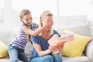 glückliches Mädchen, das ihre Mutter mit Geschenk zu Hause überrascht