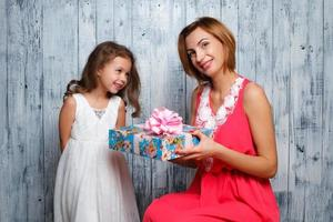 kleines Mädchen, das ihrer Mutter ein Geschenk gibt, der Tag von foto