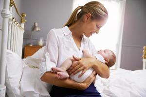 Mutter gekleidet für die Arbeit, die Baby im Schlafzimmer hält foto