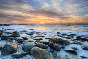 runde Steine, die bei Sonnenuntergang von der Flut eingetaucht werden foto