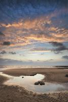 atemberaubende lebendige Sonnenuntergangslandschaft über Dunraven Bay in Wales foto
