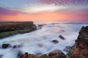 atemberaubender Sonnenaufgang und Ozean fließen über Gezeitenfelsen foto
