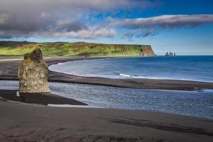 großer Felsen am schwarzen Strand in Island