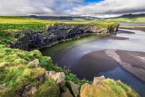 kleine Klippen und Bucht mit schwarzem Sand in Island