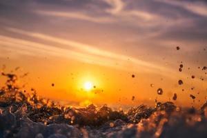 Sonnenaufgangslicht, das auf Ozeanwelle mit Orangetönen scheint