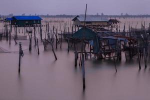 Holzpier auf einem blauen See Sonnenuntergang und bewölkt sk foto