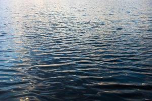 Wasseroberfläche mit Wellen und Sonnenstrahlen Reflexionen foto