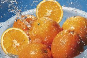 Wasser spritzt auf frische Orangen im Sieb