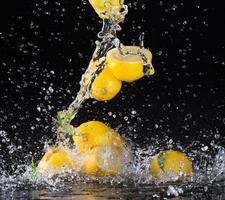Zitronen im Wasser spritzen auf schwarzem Hintergrund