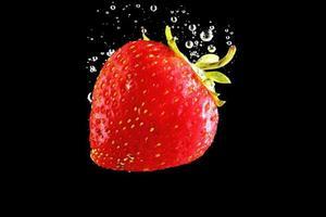 Erdbeere, die in Wasser am schwarzen Hintergrund fällt
