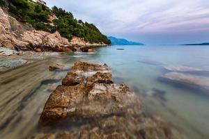 felsiger Strand und transparentes adriatisches Meer in der Nähe von Omis