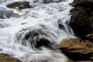 Wasser fließt über Felsen im Strom