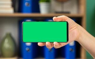 Frau, die horizontales grünes Bildschirm-Mobiltelefon hält
