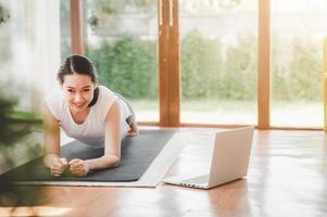 Frau, die Planke auf einer Yogamatte tut