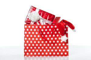 rote Geschenkboxen und und Weihnachtsmütze in Einkaufstüten foto