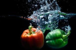 Paprika fallen ins Wasser auf schwarzem Hintergrund.
