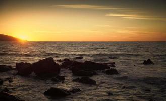 Küstensteine und Meerwasser bei Sonnenuntergang, Marokko foto