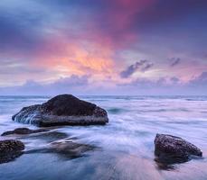 Wellen und Felsen am Strand des Sonnenuntergangs foto