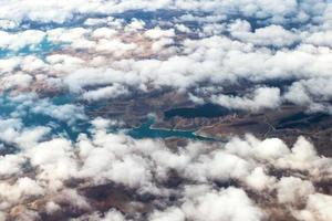 weiße Wolken über dem sandbraunen Land und den blauen Flüssen