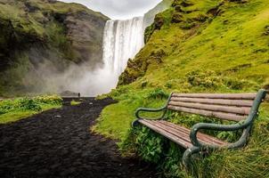 Landschaftsansicht des wilden Skogafoss-Wasserfalls und der Bank