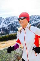 junge Frau, die in den Bergen am sonnigen Wintertag läuft