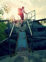 Der große Rucksacktourist hält den Handlauf auf einem Felsen. sonniger Tagesanbruch in Felsen.