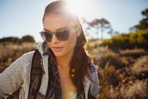 Frau, die in einem sonnenbeschienenen Naturschutzgebiet wandert foto