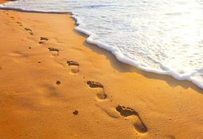 Strand, Welle und Schritte zur Sonnenuntergangszeit foto